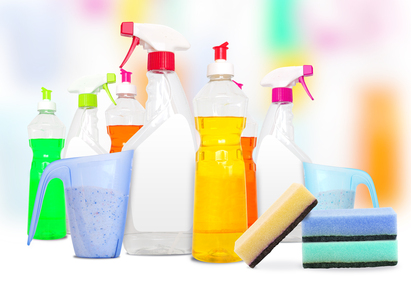 Many colorful bottles of cleaning products and spounges